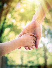 une main d'enfant qui tient la main d'un adulte
